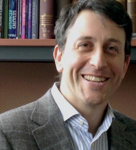 Prof. David Fisman smiling head shot in front of bookshelf