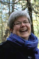 head shot, laughing, purple scarf, woods in background, short grey hair, glasses