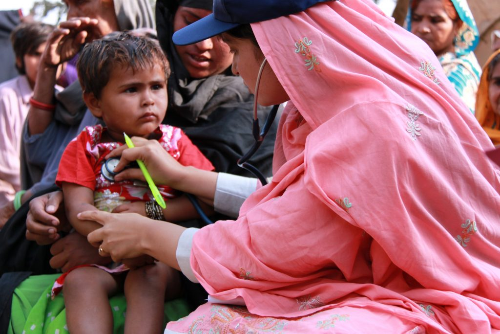 A female doctor with the International Medical Corps examines a young boy at a mobile health clinic in the village of Goza, near Dadu, in Pakistan's Sindh province. Funding from the UK government is enabling the International Medical Corps to operate mobile health clinics in Sindh, as part of the UK's response to the Pakistan floods. These clinics will provide access to basic healthcare services for thousands of people across Sindh as they return home to communities which were devastated by the floods in August 2010. The floods destroyed clinics and hospitals as well as homes and schools, so mobile teams of doctors, nurses and pharmacists are a vital way of reaching people in need of healthcare. The teams also operate as a disease 'early-warning' system; being getting out into the communities, they can spot the early signs of cholera and other water-borne diseases associated with large amounts of standing water and limited sanitation.