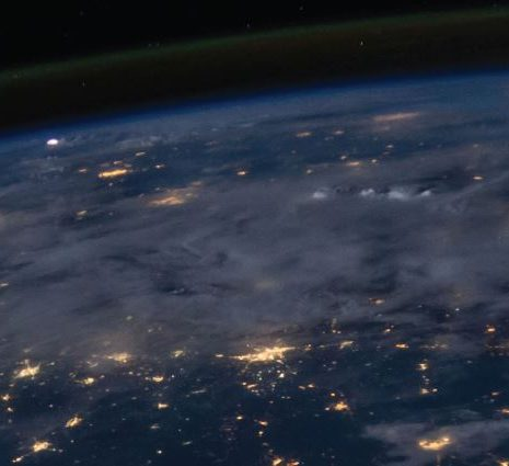 The earth from outer space, looking at the clouds and cities from above.