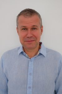 head shot of Prof. Peter Juni wearing blue button down shirt