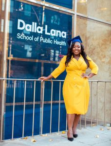A photo of Maame De-Heer infront of the Dalla Lana School of Public Health building