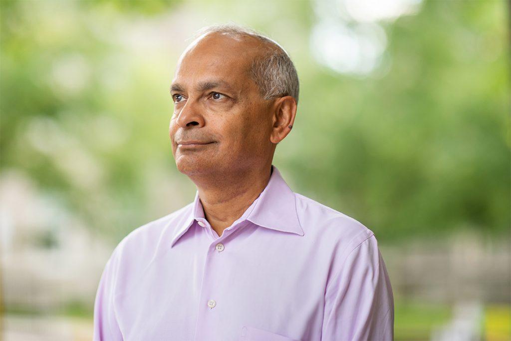 Prof. Vivek Goel headshot, in pastel purple shirt, blurred trees in background