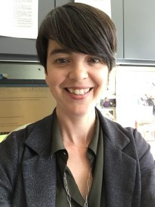 head and upper body shot of Jen Brooks wearing black shirt with open collar and smiling