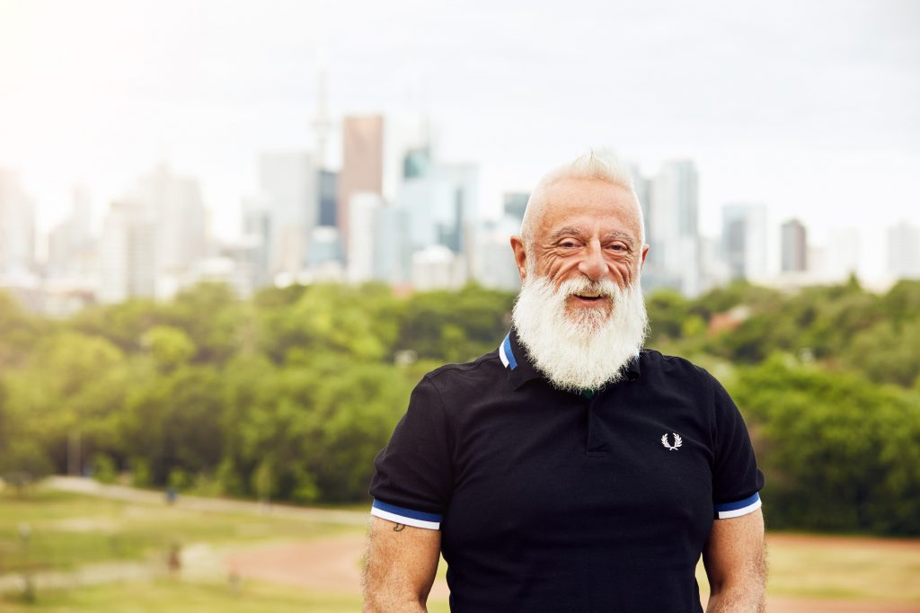 portrait of Francisco in a short sleeved dark polo shirt standing in front of a Toronto skyline