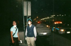 Heidi Singer at Ground Zero with mask under her chin and dust covering car behind her